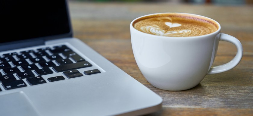A cup of coffee and laptop sit on a coffee shop table.