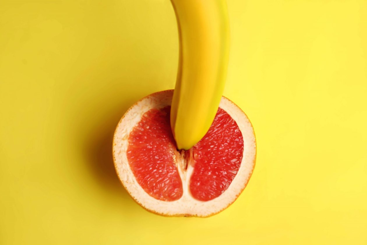 A grapefruit half with the tip of a banana pushing into the middle - implying penetration. Photo.