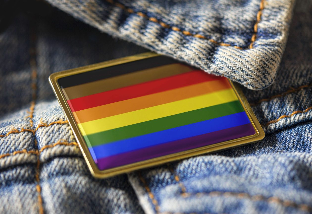 Philadelphia pride flag pinned to a denim jacket. Photo.
