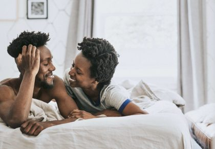 Black couple in bed together, laughing and being intimate. Photo.