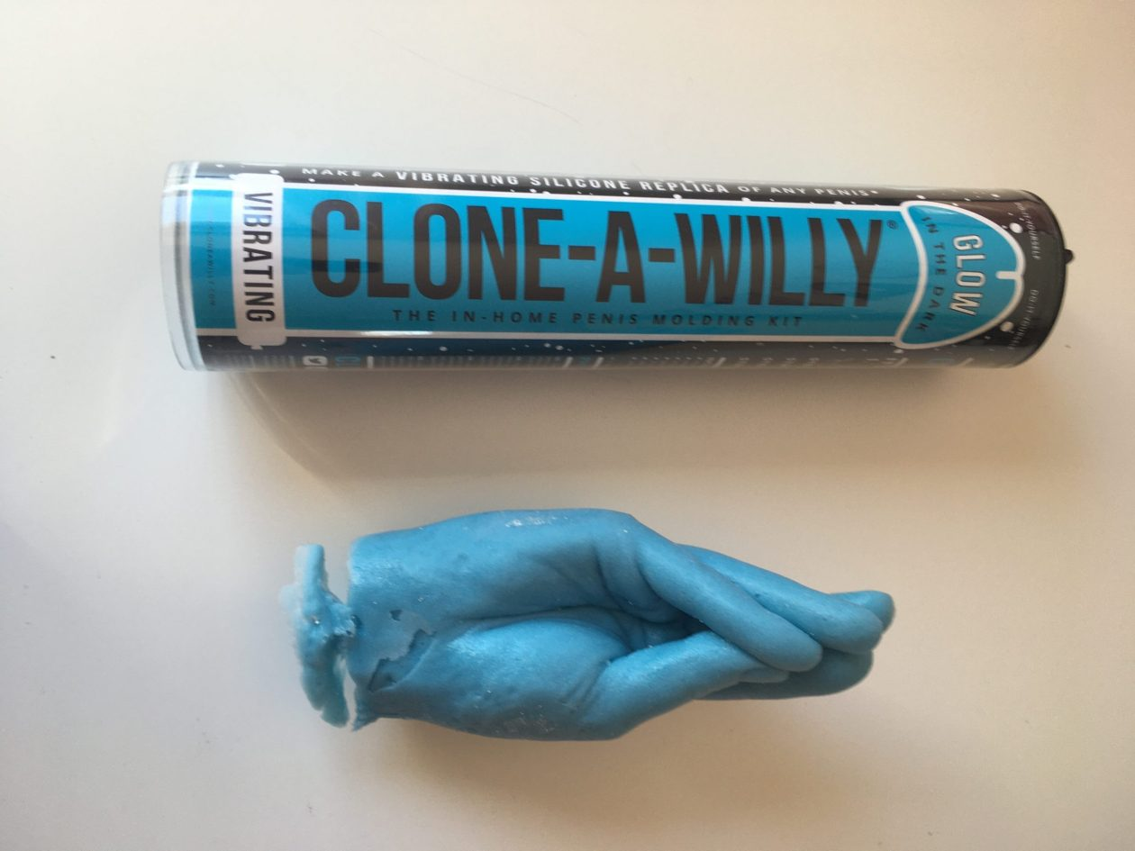 A Clone-A-Willy kit sits next to a blue silicone copy of my fist. Photo.