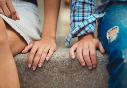 An afab and amab person sit next too each other on a stone step, their hands side by side but not touching. Photo.
