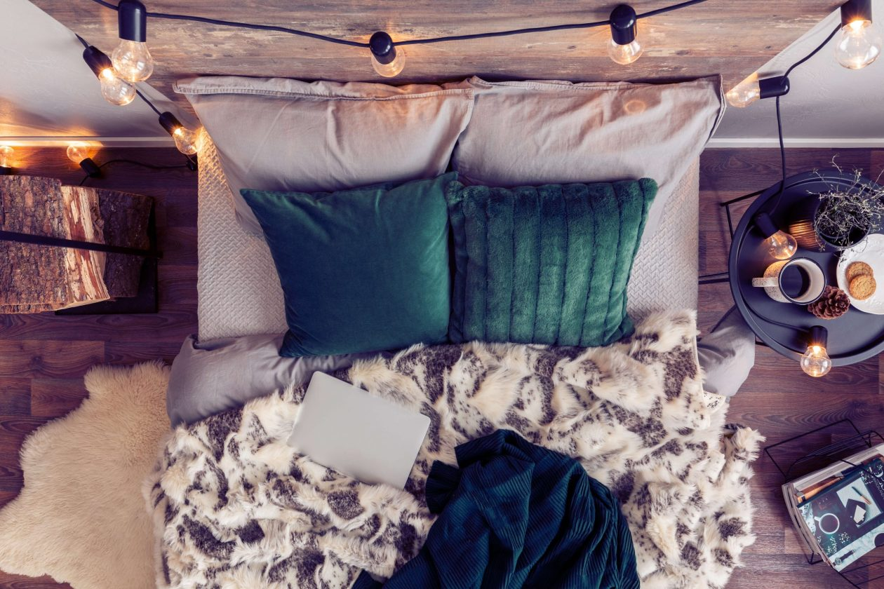 Top view of comfortable, perfectly made bed with emerald green pillows, fury duvet and closed laptop. Photo.