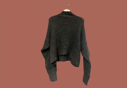A dark grey knitted jumper on a hanger in front of a pink background. Photo.