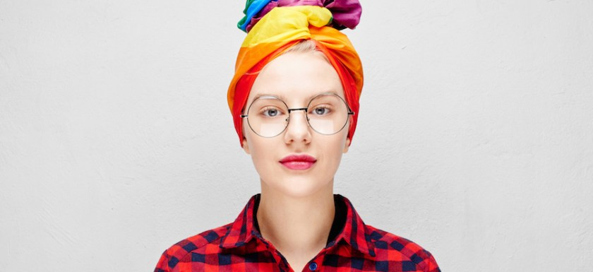 A pretty young afab person with round glasses and full lips wears a rainbow turban and a red shirt. They are smiling against a white wall. Photo.