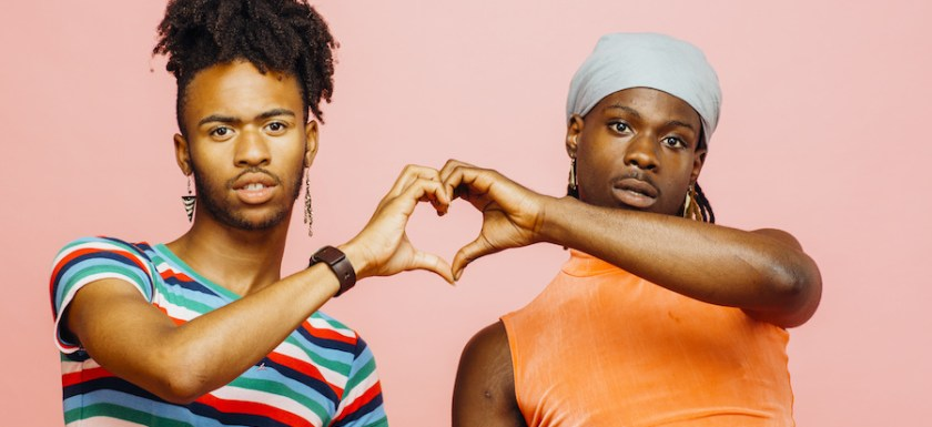 Two Black gay men hold hands, with their other hands together forming a heart. Photo.