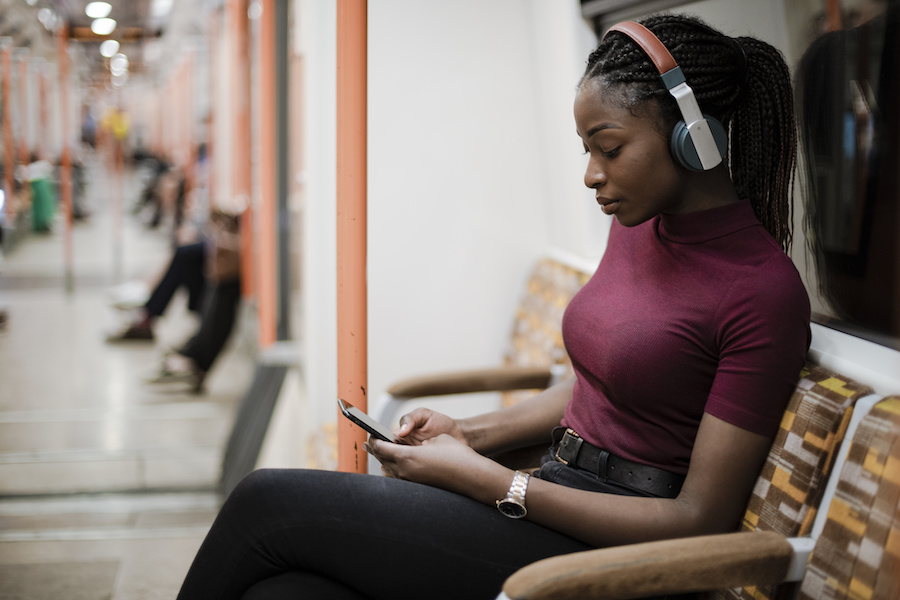 A Black woman with braids sitting on an underground train. She's wearing headphones and looking at her phone. Photo.