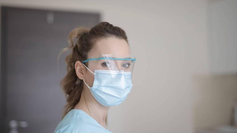 Verzorgende met mondkapje en oogbescherming