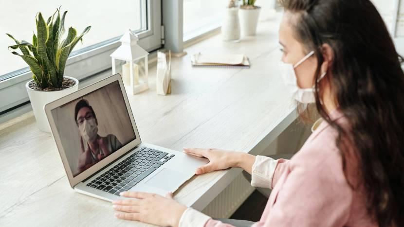 Twee personen met mondkapjes die met elkaar videobellen op een laptop
