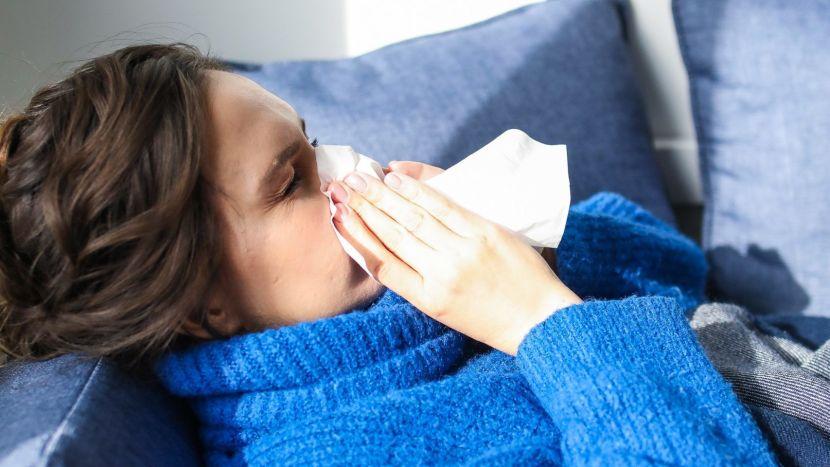 Vrouw die ziek in bed lig die haar neus snuit
