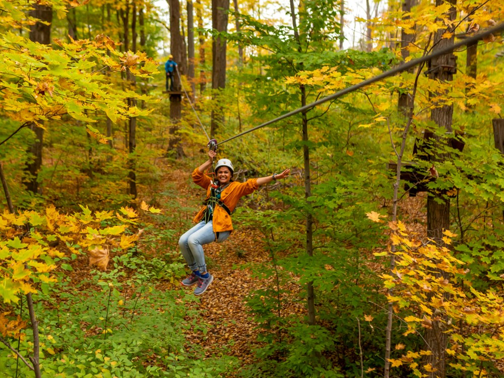 Woman ziplining with Treetop Trekking
