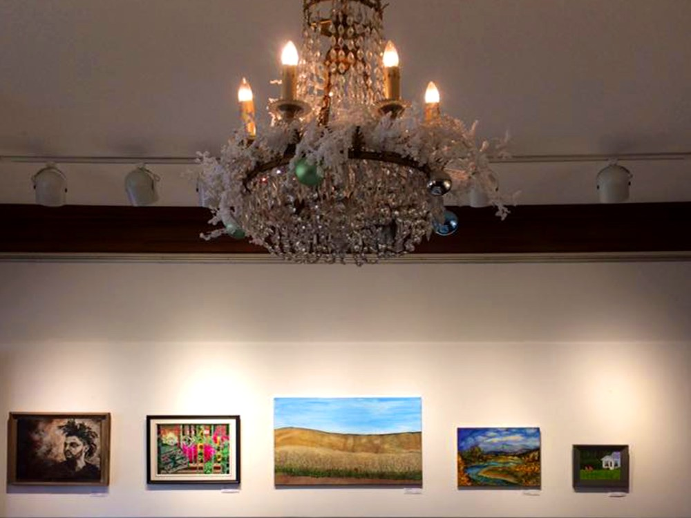Wall of art, with a lovely chandelier with seasonal decorations