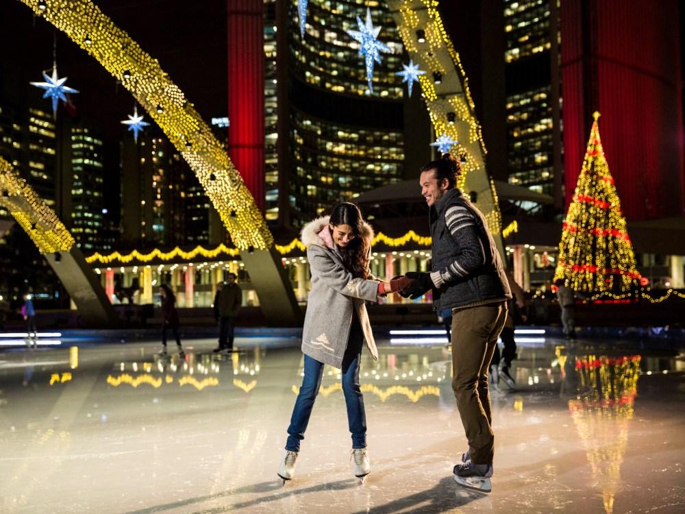 Couple skating at Nathan Phillips Square under magical lights