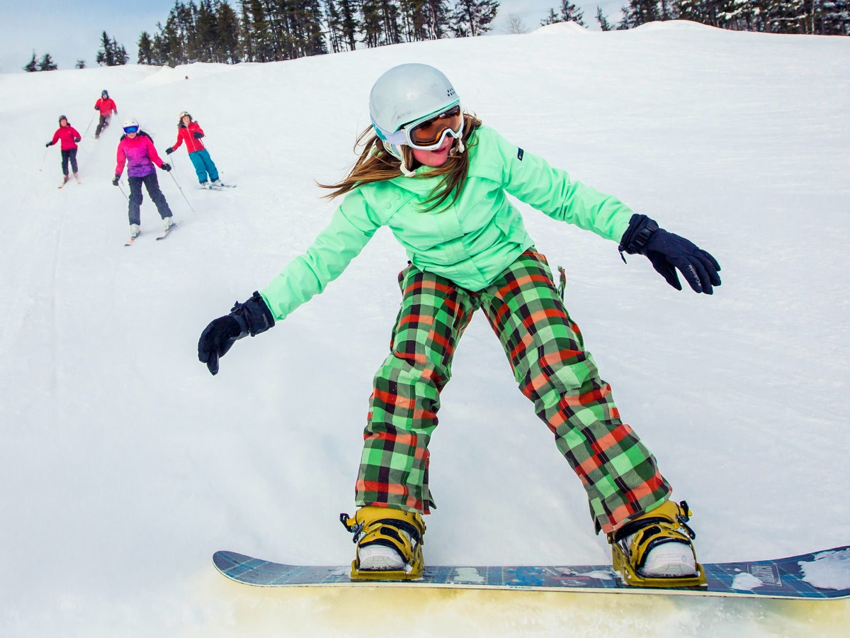 Young girl snowboarding down a hill, with a family skiing down the hill behind her.