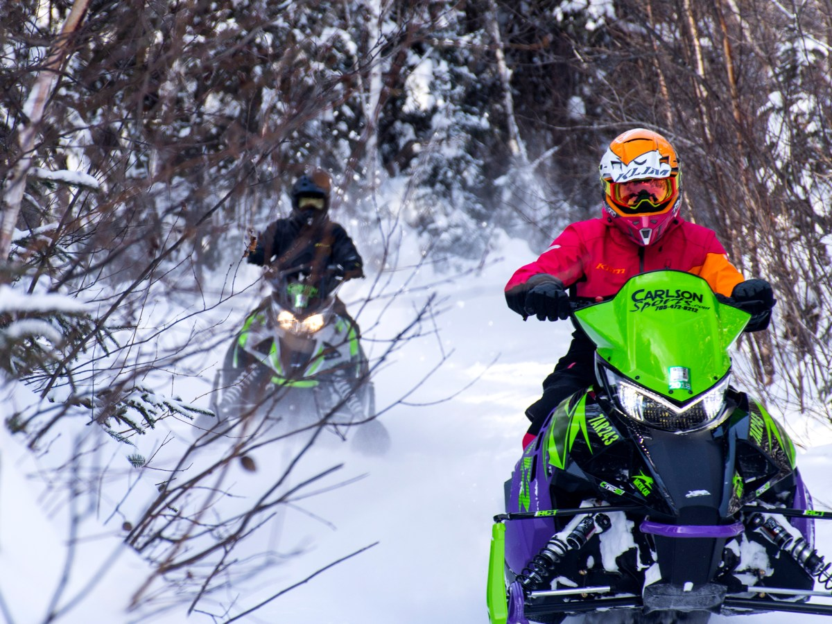 Two people snowmobiling through the forest.