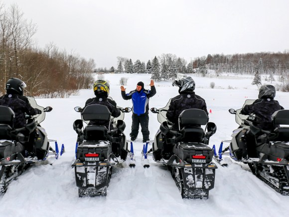 Beginner snowmobilers getting instructions before ride