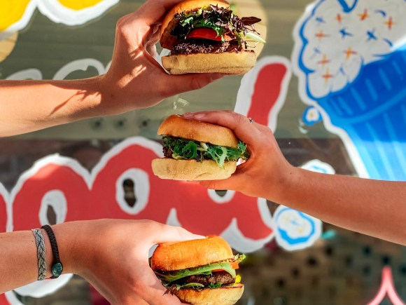 Three people holding up delicious looking burgers
