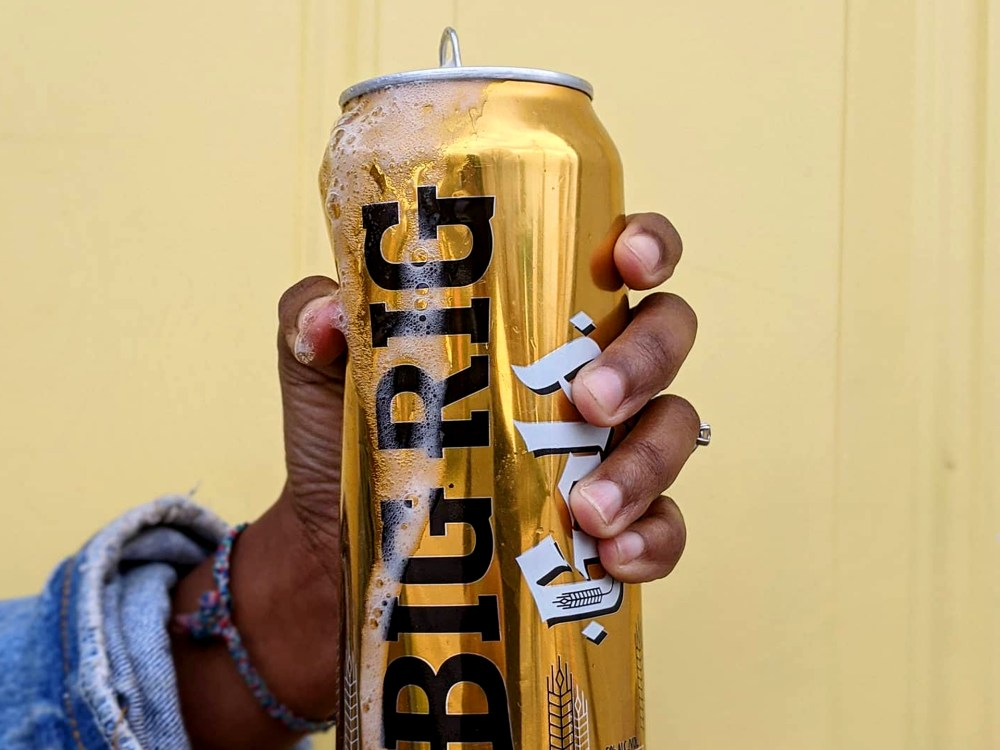 Close up of a woman's hand holding a can of beer