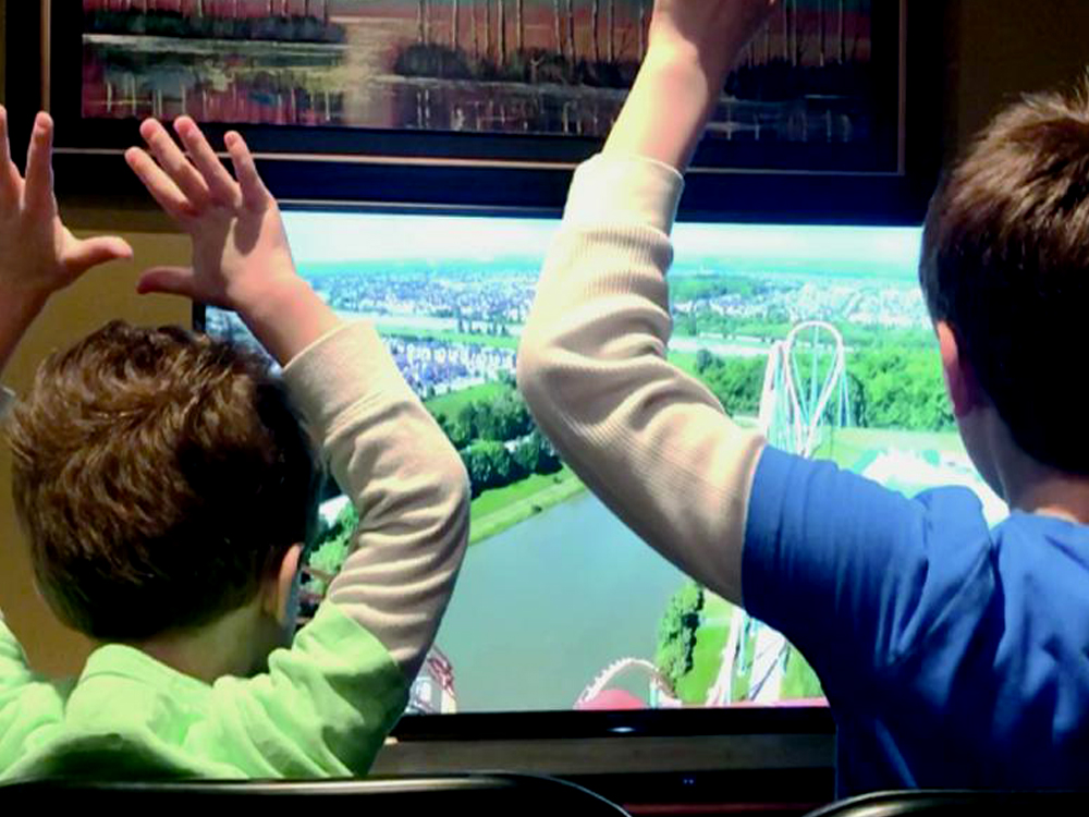 Two kids sitting in front of a tv riding a virtual roller coaster