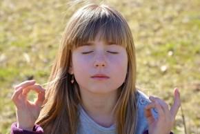 Een meisje die met gesloten ogen aan het mediteren is.