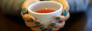 Handen die een kop thee vasthouden