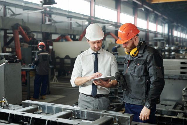 Young master in hardhat and bearded engineer discussing technical sketch on display of tablet in factory workshop