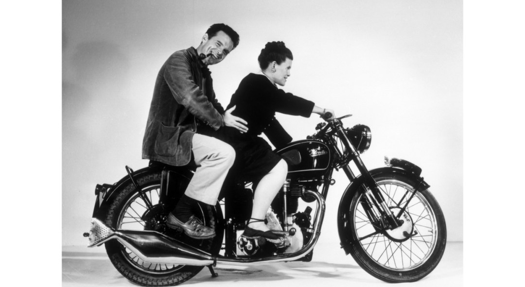 An Eames Celebration. Charles and Ray Eames posing on a Velocette Motorcycle, 1946. ©Eames Office LLC