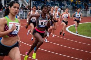 runners running on a burnt orange track