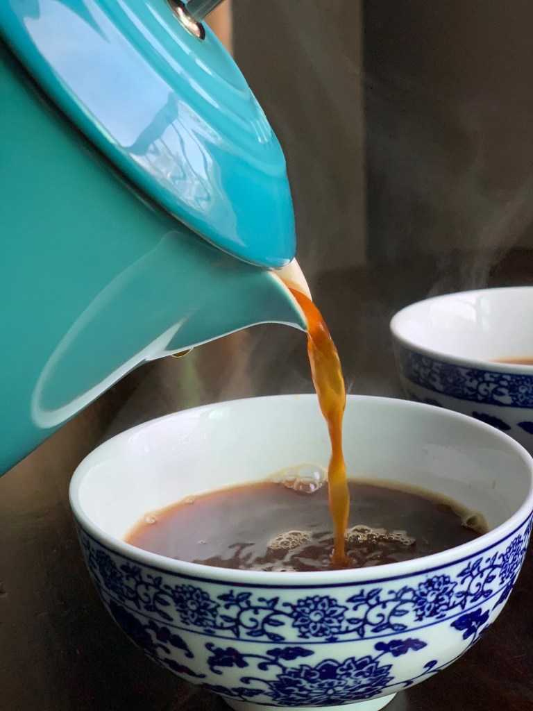 a blue french press pouring hot coffee