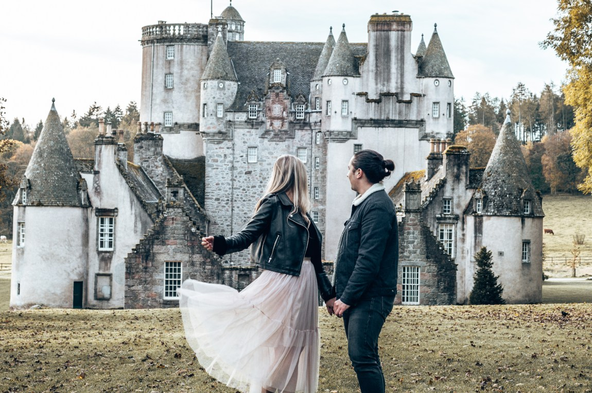 couple in front of castle fraser in scotland