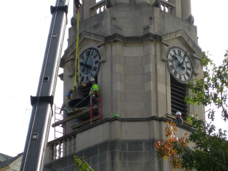 Workers remove the bell from its housing in Old Main's  Tower.