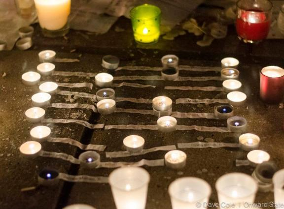 The names of each victim from the Newtown, CT shooting is placed beside among candles (Photo by Dave Cole)
