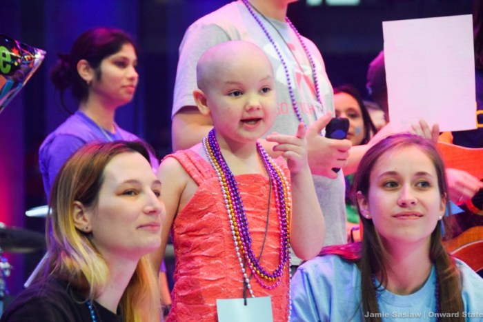 Dancers hang out on stage with a THON child.