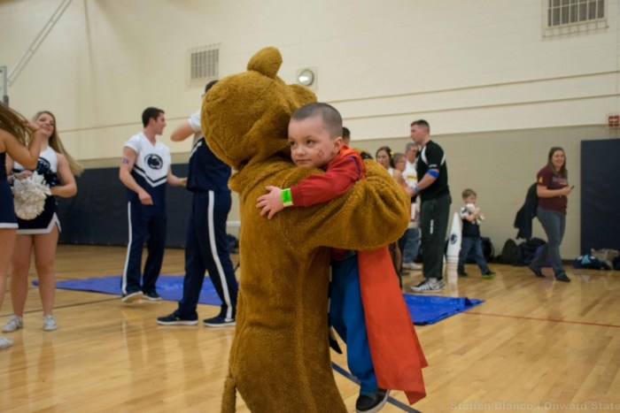 A small superhero hugs the Nittany Lion at Athlete Hour.