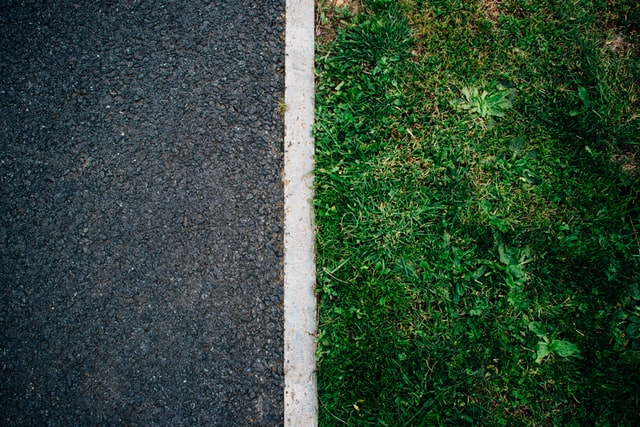 asphalt and white line and green grass