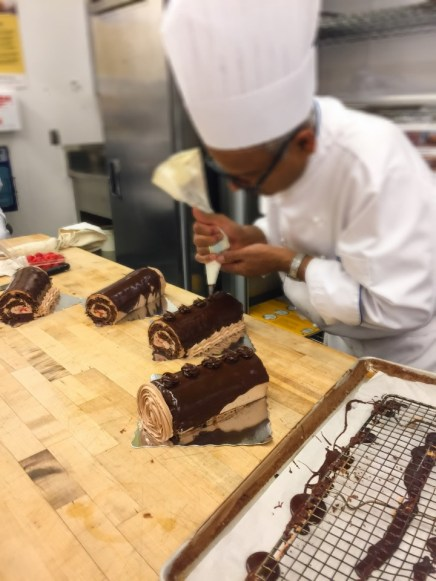 Chef is piping rosettes with the chocolate glaze.