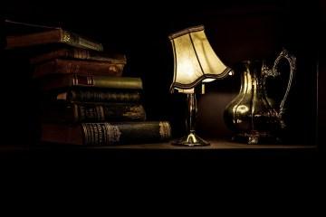 table sur laquelle repose une lampe, une théière et des livres