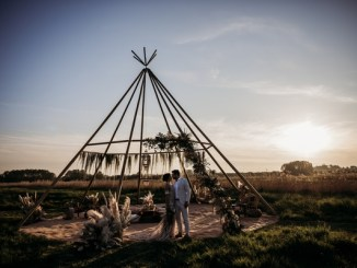 Couple standing under a tipi at sunset