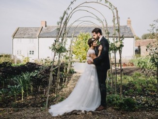Married couple stood under archway