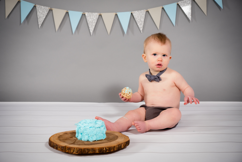 One year old and his blue smash cake at Open Box Photography studio in Dexter