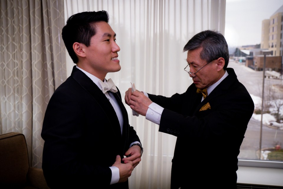 Groom's father helping with groom's bow tie