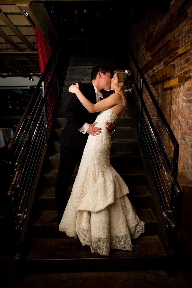 Bride and groom dip and kiss at Vinology
