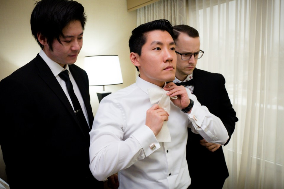 Groom with his groomsmen tying a bow tie