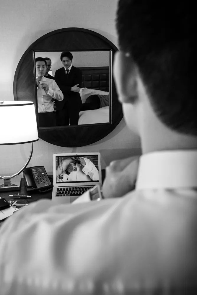 Black and white of groom tying his bowtie