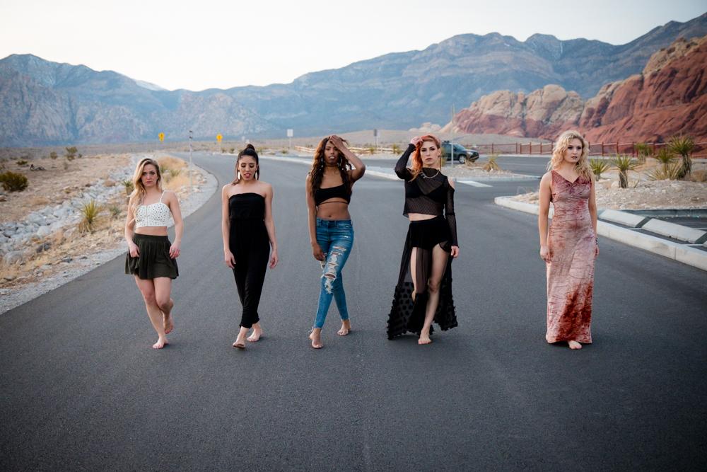 Five dancers walking down a desert road