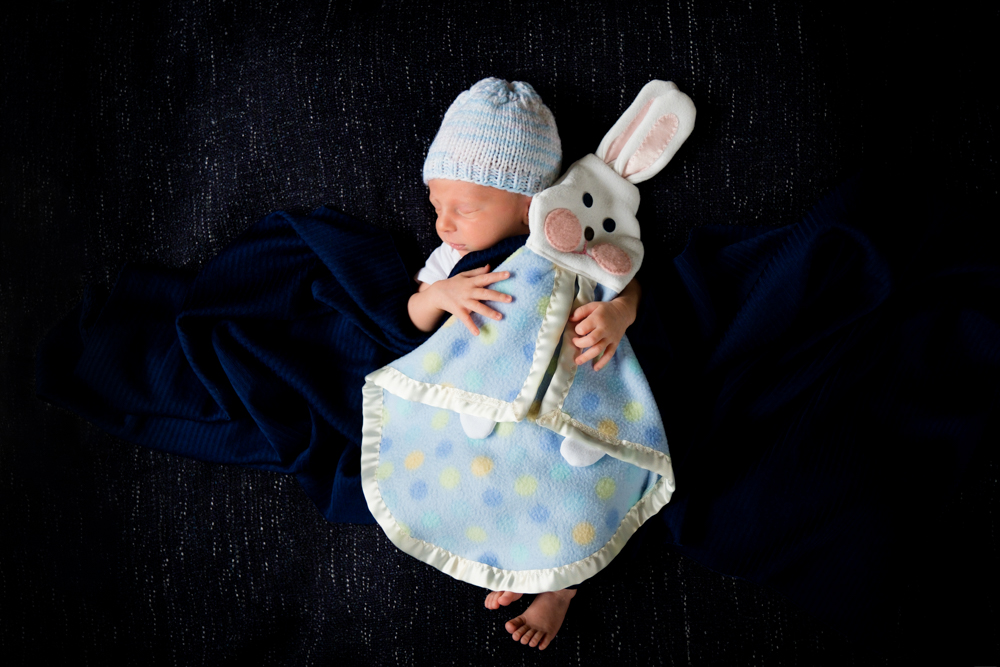 Newborn boy wrapped up holding a bunny blanket