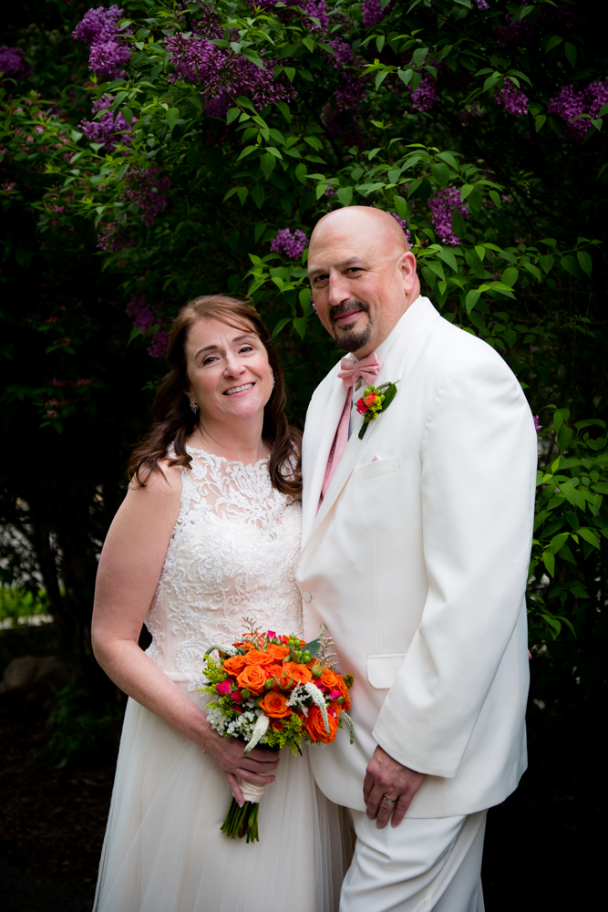Bride and groom together smiling in front of a lilac bush