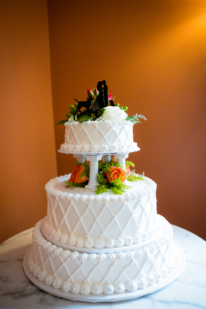 Beautiful two tiered white wedding cake with orange flower accents