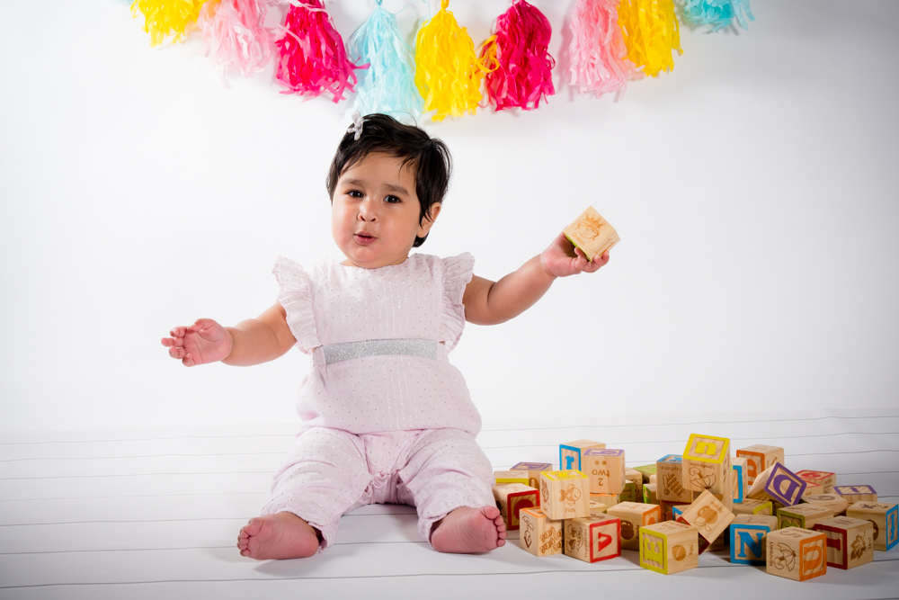 Little girl holding blocks sitting.
