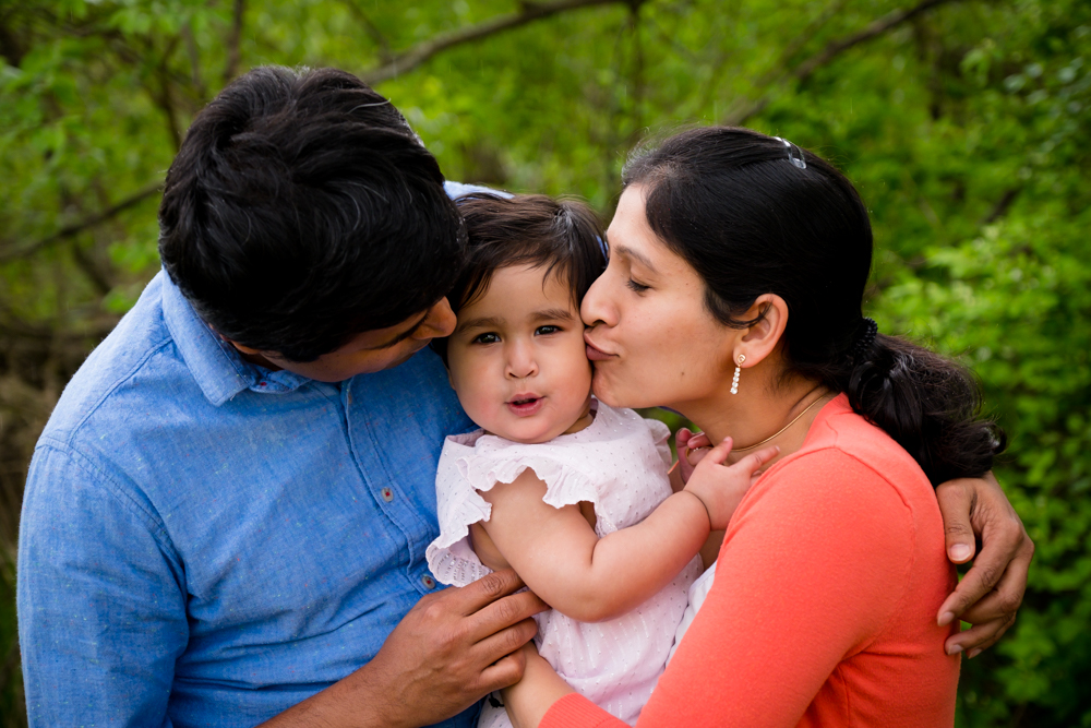 One year old girl looking at the camera while being kissed by her mom and dad.